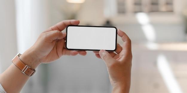 Großaufnahme des mannes horizontalen smartphone des leeren bildschirms halten Premium Fotos