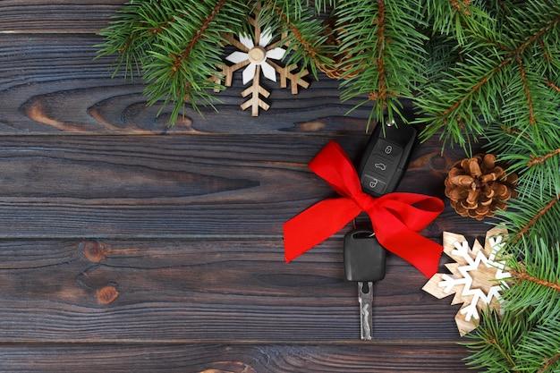 Großaufnahme von autoschlüsseln mit rotem bogen als geschenk auf holz Premium Fotos