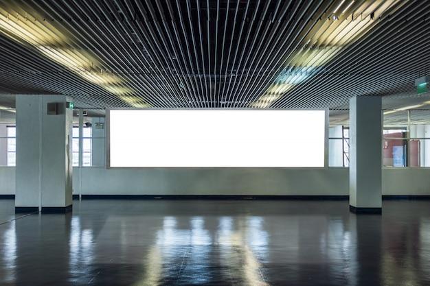 Große anschlagtafel auf metallischem designkorridor mit transparenten fenstern Premium Fotos