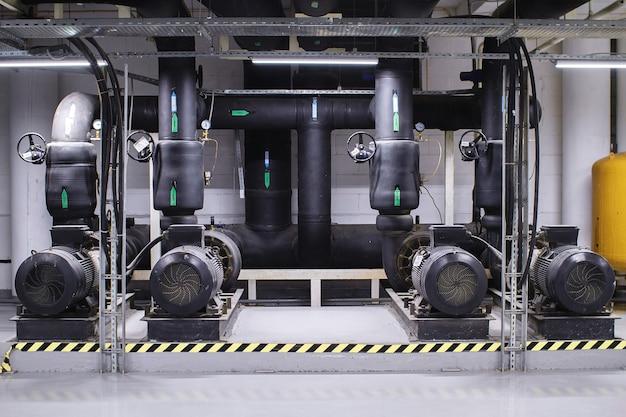 Große brauchwasseraufbereitung und heizungsraum. schwarze rohre, pumpen und ventile Premium Fotos