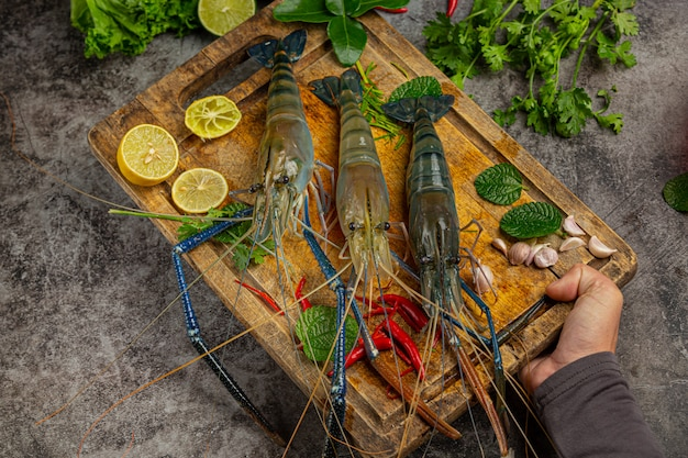 Große frische flussgarnelen bereit zu kochen dekoriert mit schönen beilagen. Kostenlose Fotos