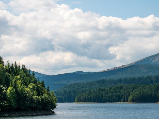 Große landschaft von rumänien mit bergen, see, bäumen und cloudsin ein sonniger sommertag Premium Fotos