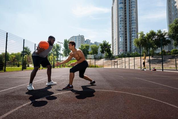 Große männer, die auf städtischem basketball spielen Kostenlose Fotos