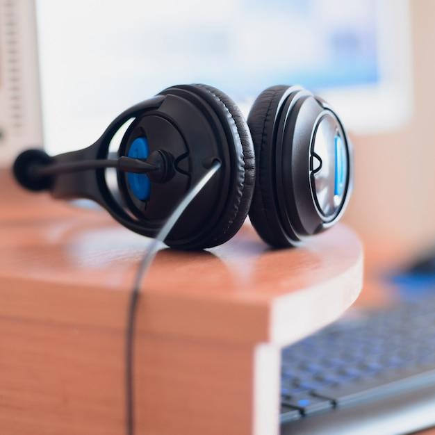 Große schwarze kopfhörer liegen auf dem hölzernen desktop Premium Fotos