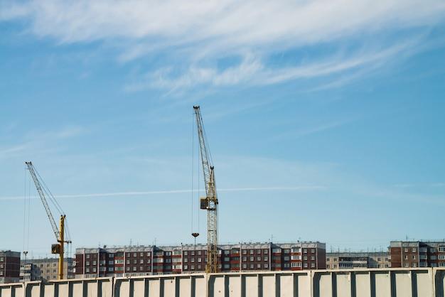 Große turmdrehkräne über im bau befindlichen gebäuden gegen blauen himmel. bild der konstruktionsnahaufnahme mit kopienraum. bau der stadt. Premium Fotos