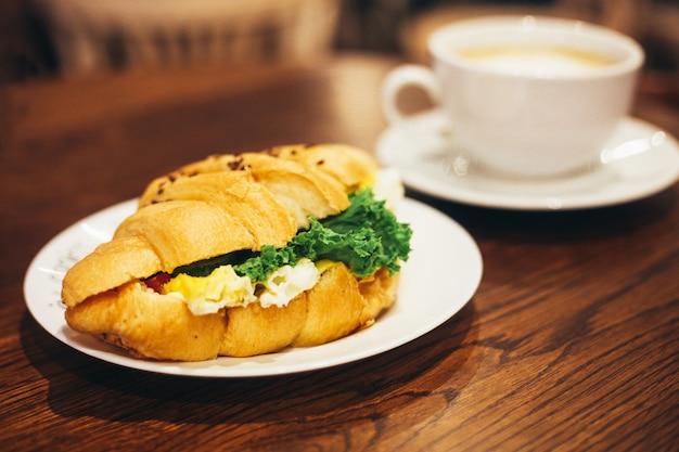Große weiße tasse kaffee und leckeres croissant Premium Fotos