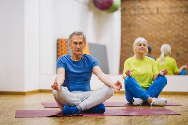Großeltern, die in der turnhalle meditieren Kostenlose Fotos