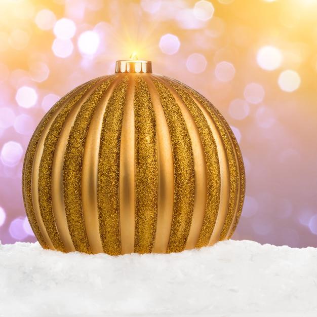 Großer goldener weihnachtsball auf schnee über festlichem defocused hintergrund mit kopieraum Premium Fotos