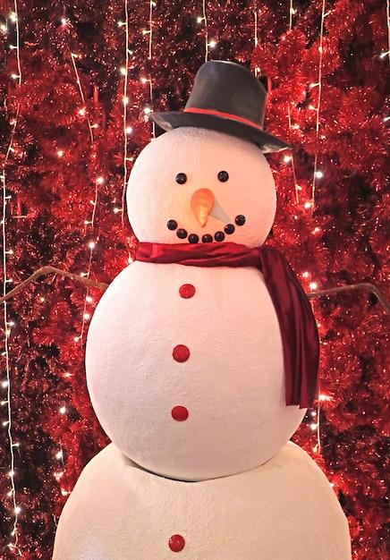 Großer schneemann vor funkelnden künstlichen roten kiefern für weihnachten Premium Fotos