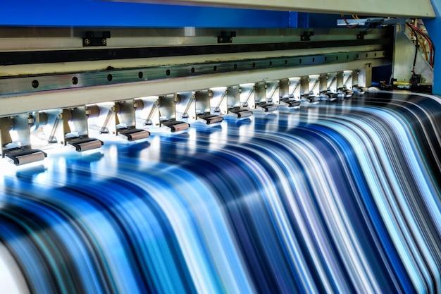 Großer tintenstrahldrucker, der mehrfarbig an vinylfahne arbeitet Premium Fotos