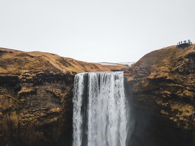 Großer wasserfall, der vom trockenen braunen berg herabströmt Kostenlose Fotos