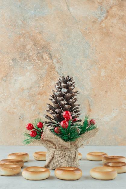 Großer weihnachtstannenzapfen mit runden köstlichen keksen auf weißem hintergrund. hochwertiges foto Kostenlose Fotos
