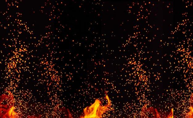 Großes brennendes lagerfeuer mit flammen und orangefarbenen funken, die in verschiedene richtungen fliegen Premium Fotos