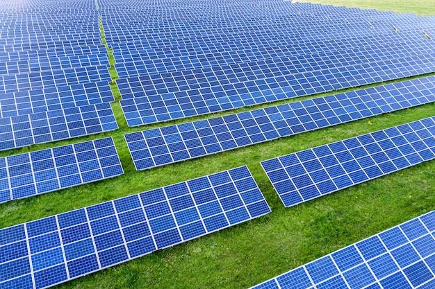 Großes feld des solarfoto-voltaic-panelsystems, erneuerbare saubere energie auf hintergrund des grünen grases produzierend. Premium Fotos