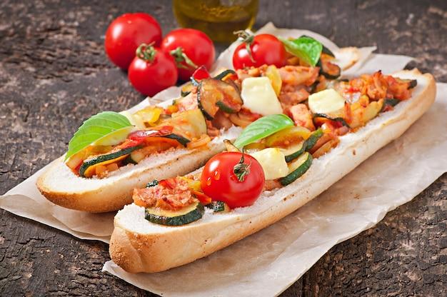 Großes sandwich mit gebratenem gemüse mit käse und basilikum auf alter holzoberfläche Kostenlose Fotos