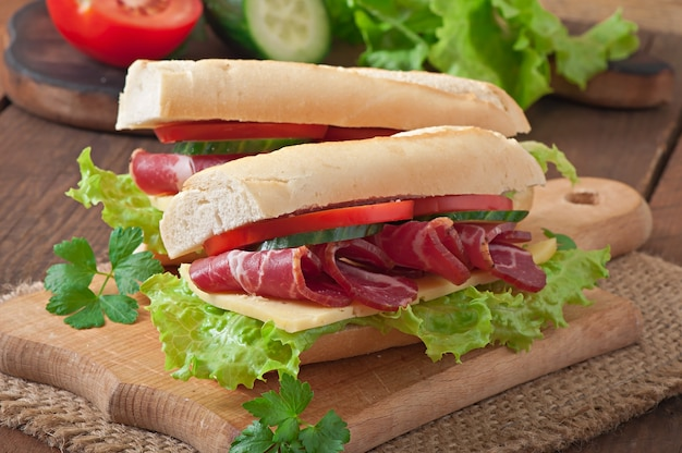 Großes sandwich mit rohem geräuchertem fleisch auf einem hölzernen hintergrund Premium Fotos