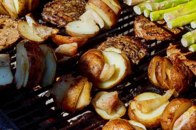 Großes stück dorf-art kartoffeln auf heißem bbq-holzkohlengrill. flammen des feuers im hintergrund. Premium Fotos