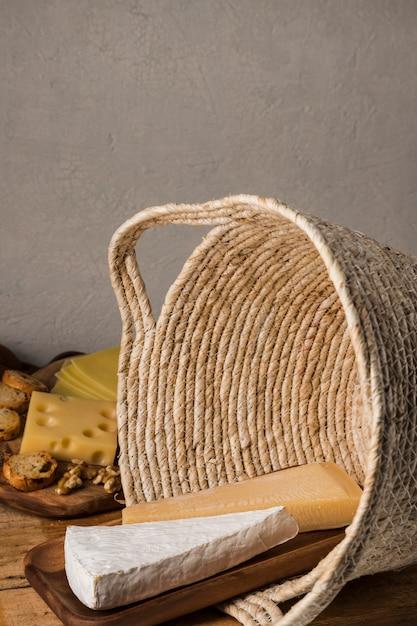 Großes stück käse auf hölzernem behälter im weidenkorb Kostenlose Fotos