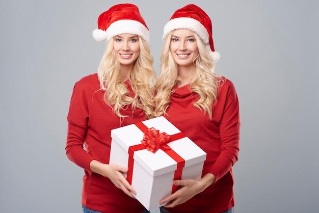 Großes weihnachtsgeschenk von zwillingen gehalten Kostenlose Fotos