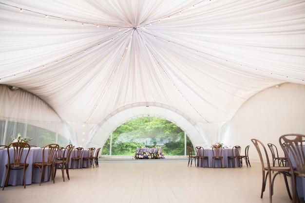 Großes weißes hochzeitszelt mit schönen dekorationen. tische mit blumenschmuck und holzstühlen Premium Fotos