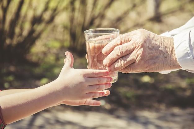 Großmutter, die einem kind ein glas sauberes wasser gibt. selektiver fokus Premium Fotos