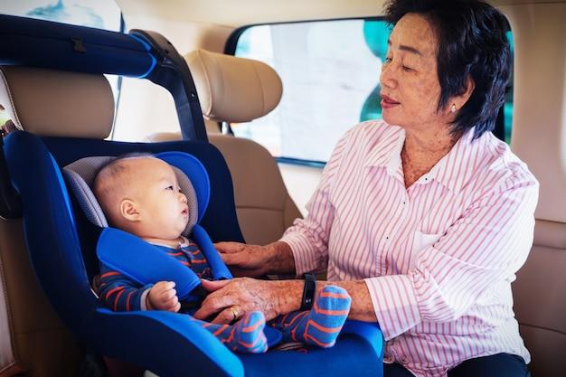 Großmutter kümmert sich um ihre kleine enkelin in einem auto, hilft ihr und jubelt auf Premium Fotos
