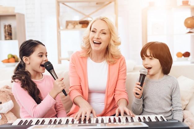 Großmutter mit den kindern, die das klavier zu hause singt spielen Premium Fotos