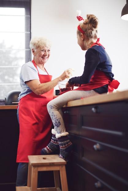 Großmutter mit mädchen kochen und genießen Kostenlose Fotos
