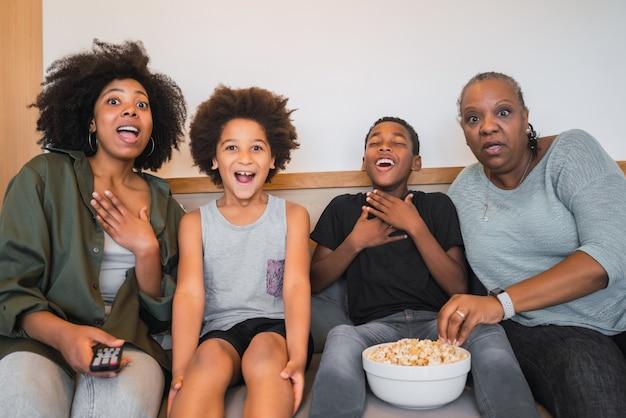 Großmutter, mutter und kinder schauen sich zu hause einen film an. Kostenlose Fotos