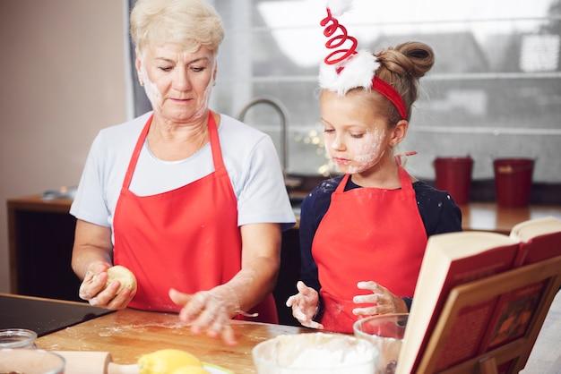Großmutter und enkelin machen teig in der küche Kostenlose Fotos