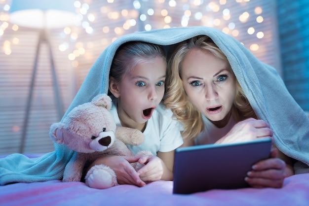 Großmutter und enkelin schauen sich einen film an. Premium Fotos