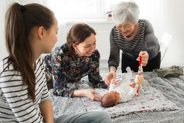 Großmutter und mutter sind glückliches baby. verwandte spielen mit einem neugeborenen Premium Fotos
