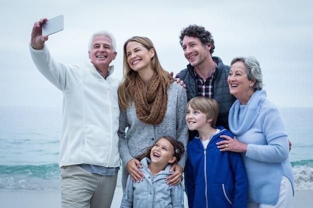 Großvater, der selfie mit netter familie am seeufer nimmt Premium Fotos
