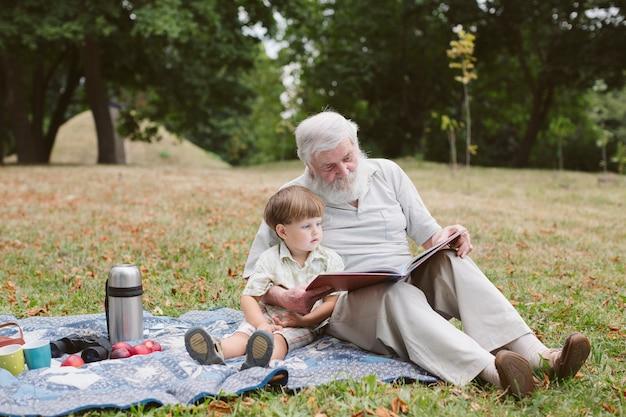 Großvater mit enkel am picknick im park Kostenlose Fotos