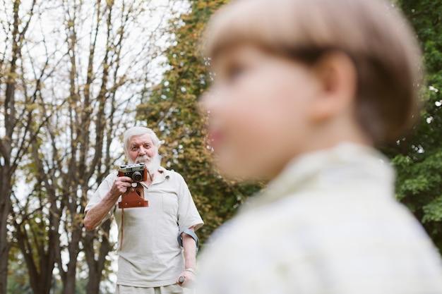 Großvater mit enkel im park, der fotos macht Kostenlose Fotos
