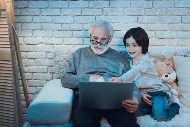 Großvater und enkel, die zusammen laptop verwenden Premium Fotos