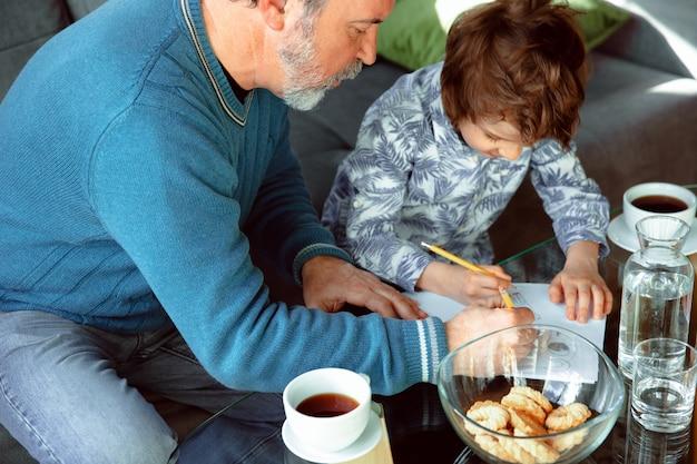 Großvater und sein enkel verbringen zeit isoliert zu hause und studieren Kostenlose Fotos