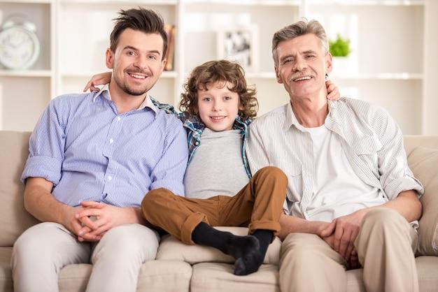 Großvater, vater und sohn sitzen auf dem sofa. Premium Fotos