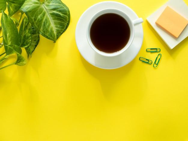 Grün lässt betriebskaffeetasse auf dem gelben desktop, ebenenlage, kopienraum. Premium Fotos