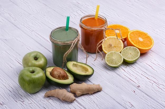Grün und orange detox coctails steht auf weißem tisch mit früchten und gemüse Kostenlose Fotos