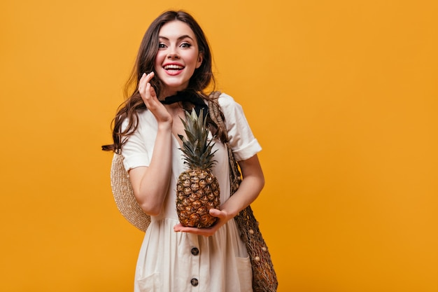 Grünäugiges mädchen im weißen kleid, das ananas hält. frau lacht und wirft mit einkaufstasche auf orange hintergrund auf. Kostenlose Fotos