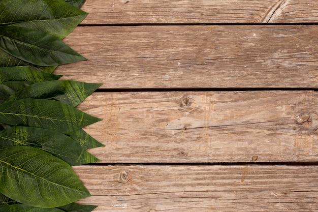 Grünblätter auf dem alten hölzernen hintergrund Kostenlose Fotos