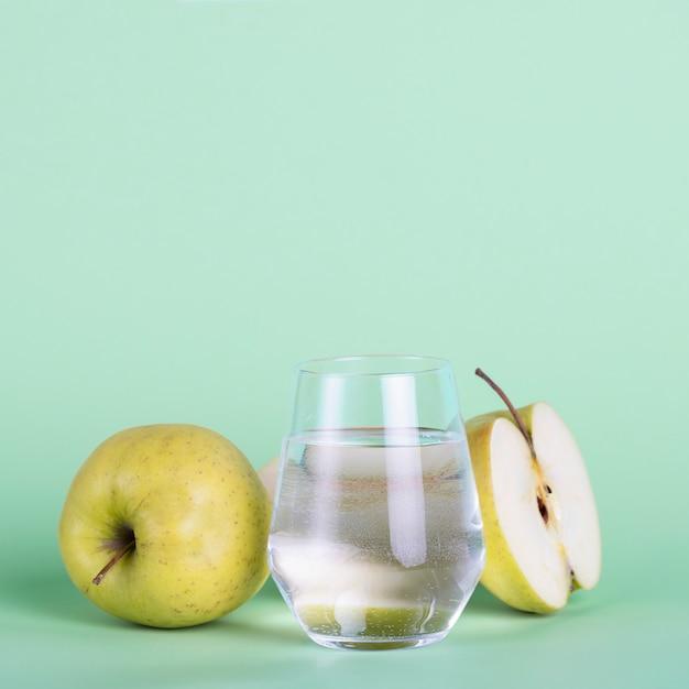 Grüne äpfel und wasserglas auf grünem hintergrund Kostenlose Fotos