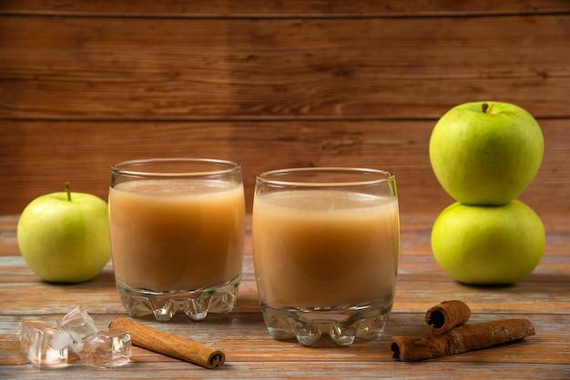 Grüne äpfel, zimtstangen und zwei tassen frischen saft auf dem tisch Kostenlose Fotos