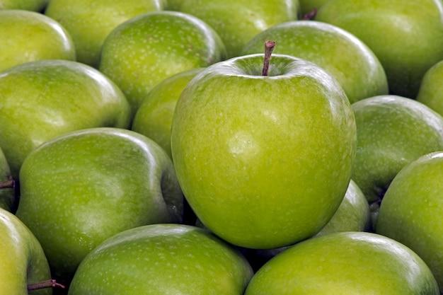 Grüne apfelnahaufnahme über stapel von äpfeln Premium Fotos