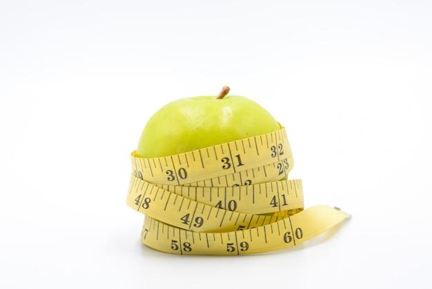 Grüne apfelverpackung durch messendes band, zum von länge auf einem weiß, diät, gesunder lebensstil zu messen Premium Fotos
