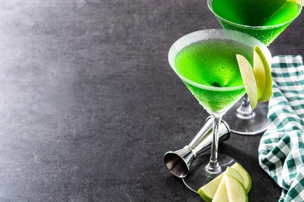 Grüne appletini-cocktails im glas auf schwarzer oberfläche Premium Fotos
