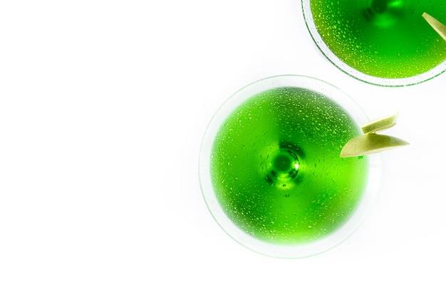 Grüne appletini-cocktails im glas lokalisiert auf weißer oberfläche Premium Fotos