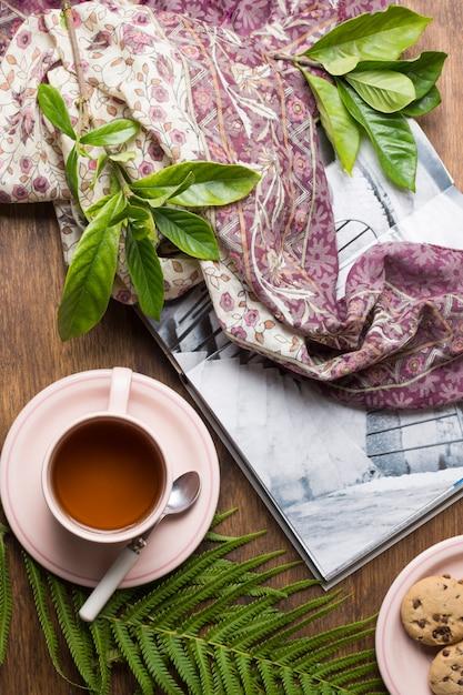 Grüne blätter auf buch; teetasse und kekse auf holztisch Kostenlose Fotos