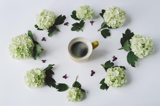 Grüne blumen in form eines kreises, der um die gelbe schale mit kaffee auf weißem hintergrund liegt Premium Fotos